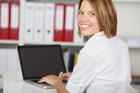 over the shoulder view: Portrait of happy businesswoman sitting in office with laptop computer, smiling at camera