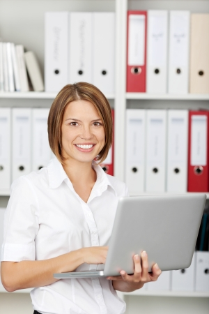 medical record: Attractive young businesswoman working on laptop, smiling, standing in office