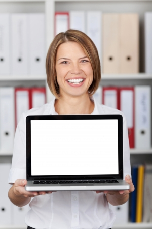 stood: Smiling woman holding a blank laptop screen turned towards the camera with white copyspace for your text Stock Photo