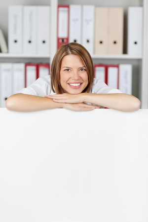 Young businesswoman with arms on white board at office - copyspace for text photo