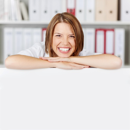 Laughing young businesswoman with arms on white board at office - copyspace for text photo
