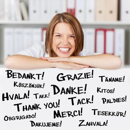 dank u: Happy jonge zakenvrouw zegt dank je wel in verschillende talen Stockfoto