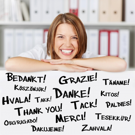 Happy young businesswoman says thank you in different languages photo