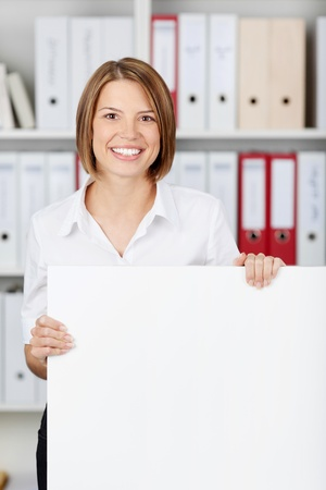 formals: Young businesswoman with big white board at office - copyspace for text