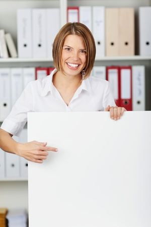 Young businesswoman show big white board at office photo