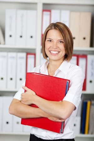 Happy young businesswoman holding a red binder photo