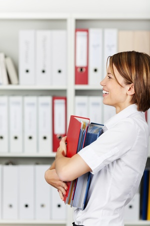 formals: Smiling businesswoman or office worker holding a stack of file folders in office