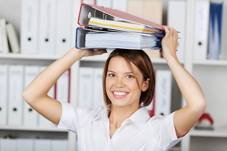 formals: Smiling businesswoman or office worker wearing a bright white blouse holding a stack of file folders over her head Stock Photo