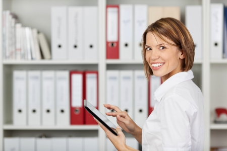 Smiling businesswoman working with ipad tablet at the office photo