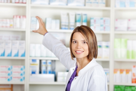 Portrait of a young woman pharmacist selecting a medication photo
