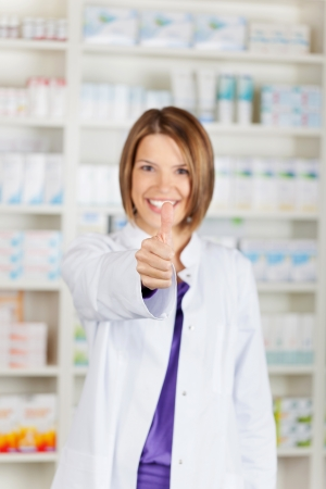 Beautiful smiling pharmacist showing thumbs up over the drugstore background photo