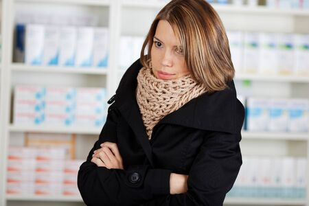 Sick woman in the pharmacy wearing a thick winter scarf and coughing while grimacing in pain Stock Photo - 21148532