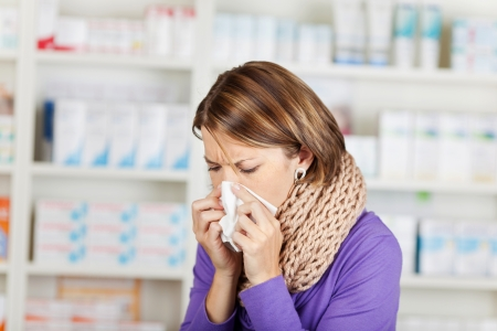 Woman with influenza in the pharmacy blowing her nose on a handkerchief and wearing a thick winter scarf Stock Photo - 21148536