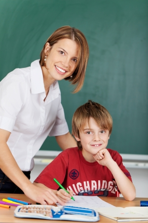 schoolroom: Smiling teacher and elementary school student during class Stock Photo