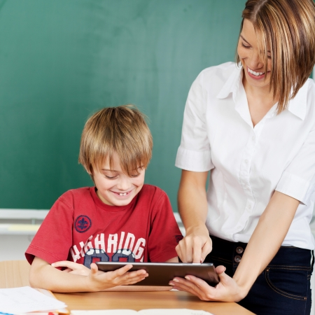 digital school: Teacher is showing tablet to student during a lesson