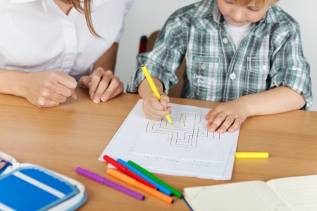 Small boy is coloring during kindergarten with teacher Stock Photo