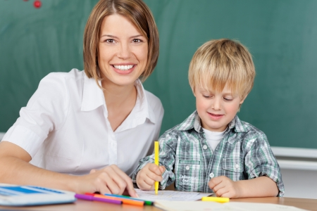 jardin de infantes: Educador sonriente con el niño en el jardín de infantes Foto de archivo