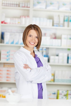 Smiling pharmacist chemist woman standing in pharmacy drugstore photo