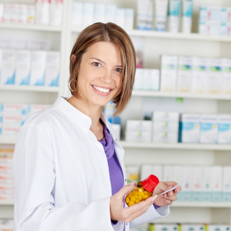 Smiling pharmacist chemist woman holding medicine in pharmacy drugstore Stock Photo - 21148557