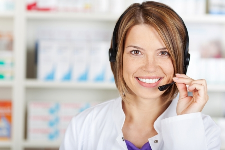 telephone saleswoman: Portrait of smiling chemist woman working with headset Stock Photo