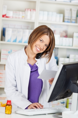 Portrait of calling female pharmacist in front of shelves photo