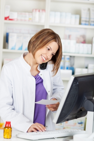 Calling pharmacist chemist while browsing on computer in the drugstore