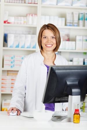 笑みを浮かべて女性薬剤師薬局薬局内部での作業 写真素材
