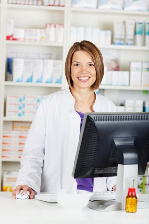 Smiling female pharmacist chemist working inside the drugstore photo