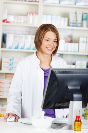 Cheerful female pharmacist chemist working inside the drugstore