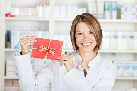 Smiling pharmacist showing a red card at the drugstore photo