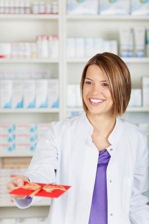 Smiling female pharmacist chemist giving a red card to someone photo