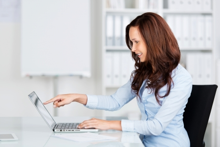enthusiastic: Profile portrait of an attractive young businesswoman pointing to her laptop as she sits at her desk