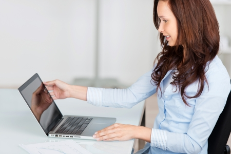 Woman working on her laptop sitting at a desk adjusting the screen position with her hand photo