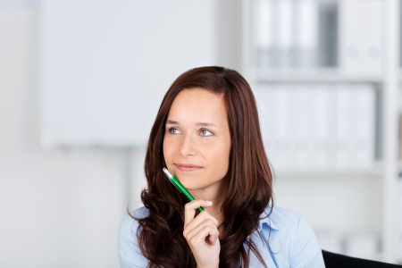 introspective: Pretty woman sitting thinking holding a pencil to her chin as she stares into the distance Stock Photo