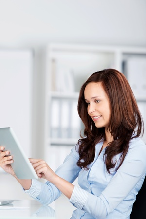 Sideways view of an attractive young woman surfing on her tablet computer using her fingertip on the touchscreen Stock Photo - 21148592