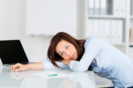 near side: Bored businesswoman relaxing in her chair with her head lying on the desk