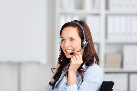Smiling friendly woman wearing a headset sitting in an office, conceptual of customer support, receptionist or a call centre operator photo