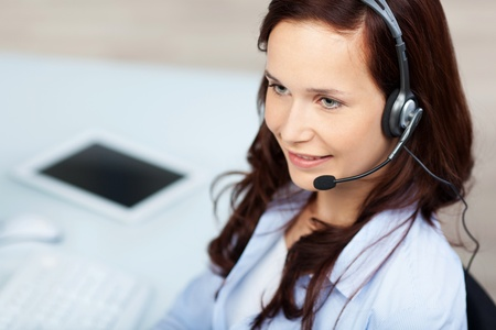 Smiling call center agent working with headset photo