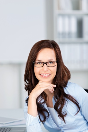 Smiling businesswoman with glasses posing in a close up shot photo