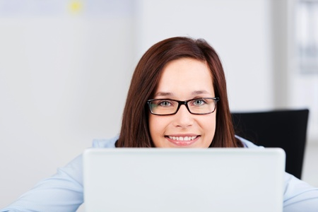 Cheerful smiling woman looking out with laptop in a close up shot Stock Photo - 21148637