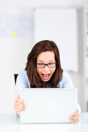 woman screaming: Portrait of screaming businesswoman looking at her laptop on the table Stock Photo