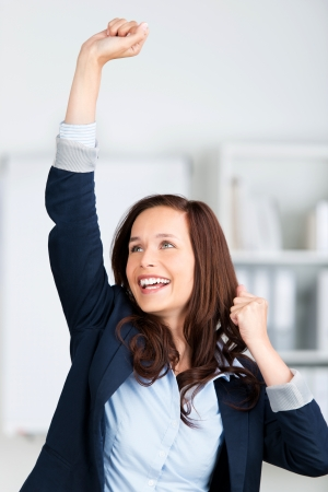 Successful businesswoman raising her hands inside the office Stock Photo - 21148737