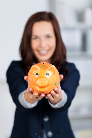 Conceptual portrait of smiling businesswoman shows the piggybank Stock Photo - 21148738