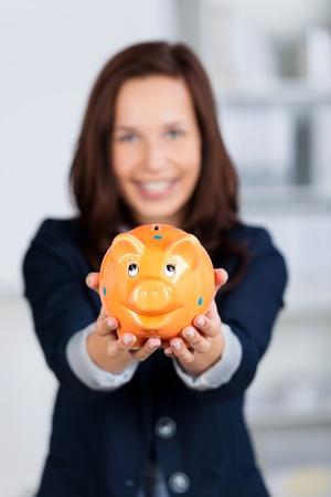 Conceptual portrait of smiling businesswoman shows the piggybank Stock Photo - 21148738