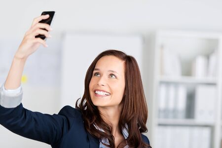 Woman photographing herself with her mobile phone holding it up in the air and smiling photo