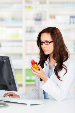 Pharmacist working on her computer checking a bottle of pills before dispensing them to a patient Stock Photo - 21148746