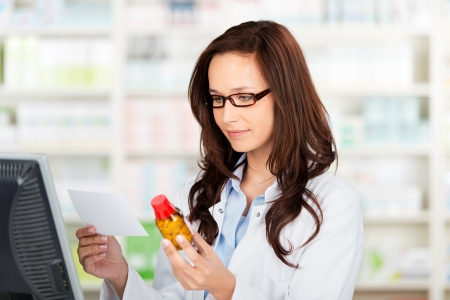 Portrait of a pharmacist checking the prescription and medication photo
