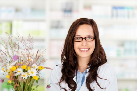 Happy pharmacist chemist woman standing in pharmacy drugstore photo