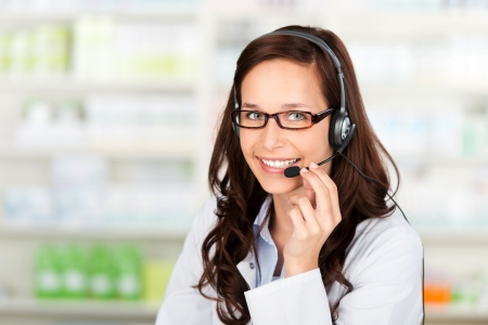 Smiling pharmacist wearing headset at the drugstore Stock Photo