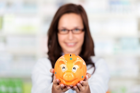Smiling Pharmacist shows a piggybank at the drugstore Stock Photo - 21148781